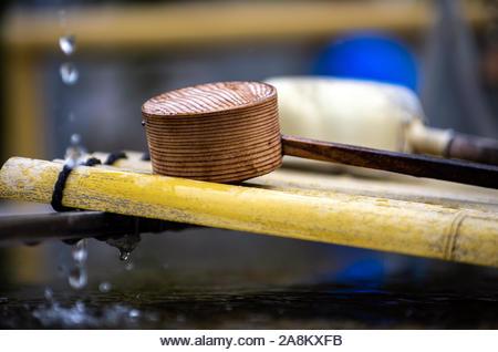Ladles line the chozuya wash basin at the entrance to Tsukiji Hongwanji Temple in Tokyo, Japan. - Stock Image