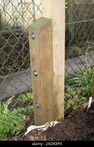 A rotten and broken fence post repaired by the addition of a wooden spur using coach bolts, England, UK - Stock Image