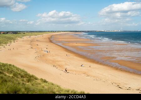 People enjoying summer sunshine on the beach north of Seaton Sluice, Northumberland, England, UK - Stock Image