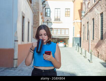 young woman with short hair, walks down a street, and drinks coffee, while talking, on her mobile phone - Stock Image