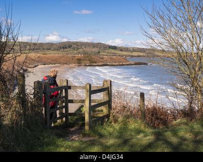 Walker walking through kissing gate on coastal path above Traeth yr Ora beach on Isle of Anglesey coast North Wales - Stock Image