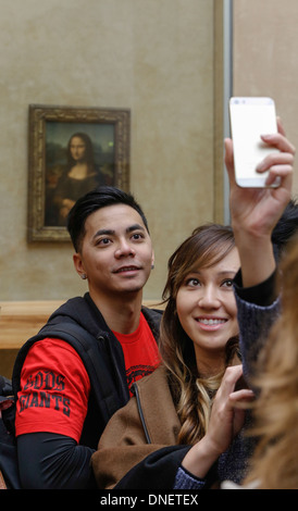 people taking selfie photos in front of the Mona Lisa painting by Leonardo da Vinci, Louvre Museum, Paris, France - Stock Image
