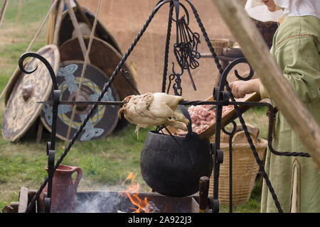 Woman dressed in medieval costume preparing food at a re-enactment camp with a spit roasted chicken and cauldron - Stock Image