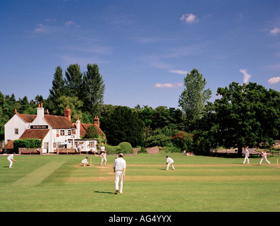 Game of village cricket Tilford Green, Surrey, England, UK. - Stock Image