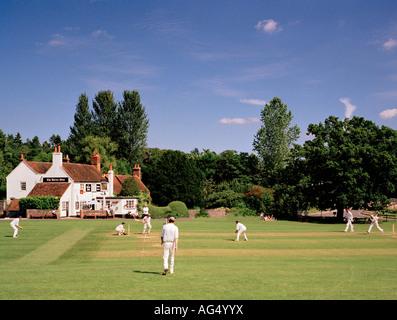 Game of village cricket Tilford Green, Surrey, England, UK. - Stock Image