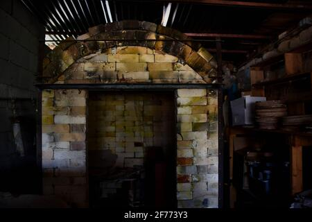 Abandoned pottery shed, looking into a kiln.  Creepy empty building. - Stock Image