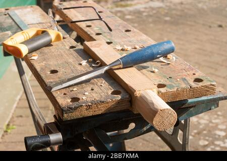 DIY a wooden worlpiece held in a Workmate vice with a wood chisel, saw and spectacles in the background - Stock Image