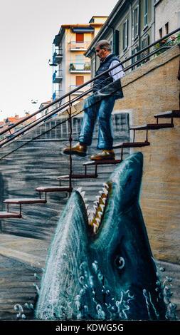 Surreal graffiti in Milan, Italy's Bohemian Navigli district - Stock Image