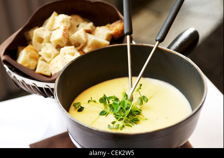 Cheese fondue plate with bread at a restaurant. - Stock Image