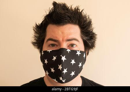 A man in his late thirties with a reusable face mask looking directly at the viewer during the Covid 19 Coronavirus pandemic with crazy lockdown hair - Stock Image