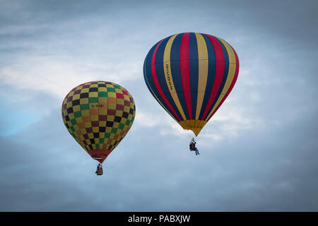 Two small hot air balloons rise into the air at the York Balloon Fiesta on the Knavesmire in York, UK. - Stock Image