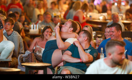 Tourists passing their holidays in Magaluf meet to watch on giant tv screens the Champions League soccer Fin - Stock Image