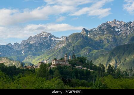 Moggio Udinese (Italy) - View of the abbey (XI a.C.) of the small town of Moggio Udinese with the background of the Alps of Friuli - Stock Image