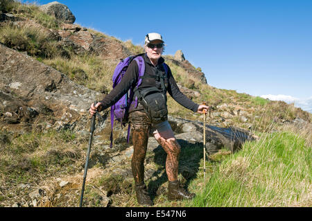 A mud covered walker after sinking in deep mud on the Dibidil to Kinloch coastal path, Isle of Rum, Scotland, UK - Stock Image