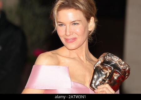 American actress Renee Zellweger showing her award at the EE BAFTA after-party dinner at the Grosvenor House Hotel in London, UK - Stock Image
