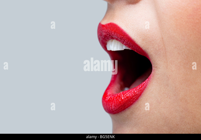 Close up of a womans mouth wide open with bright red lipstick on her lips. - Stock Image