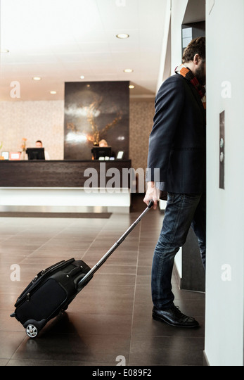 Businessman with luggage entering elevator in hotel - Stock Image