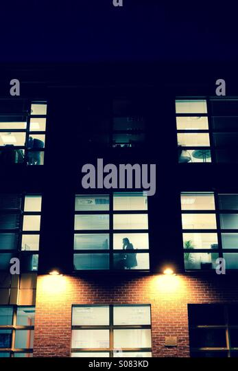 Working late again - office block at night with silhouette - Stock Image