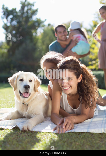 Mother, daughter and dog laying in grass - Stock Image