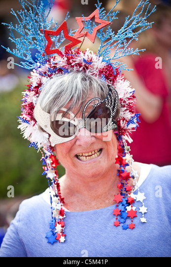 A woman dressed in patriotic costume stands in the I'On Community 4th of July parade. - Stock Image