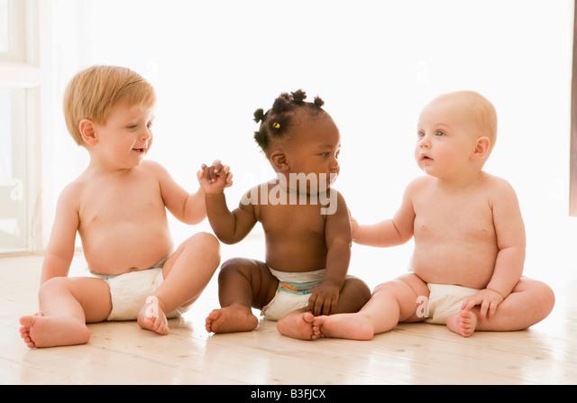three-babies-sitting-indoors-holding-han