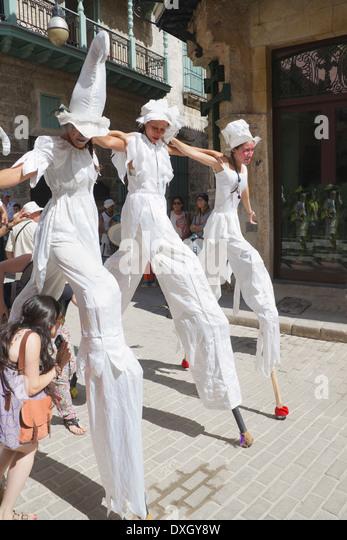 Three girls dancing on stilts in street Old Havana Cuba - Stock Image