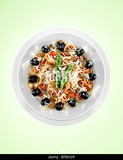 Spaghetti with black olives and asparagus indicating lunch time of one o'clock. - Stock Image