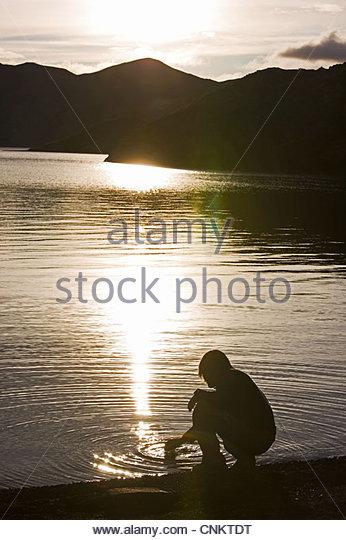 Man dipping into still lake - Stock Image