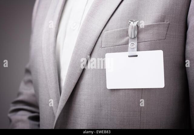 Businessman wearing blank name tag - Stock Image