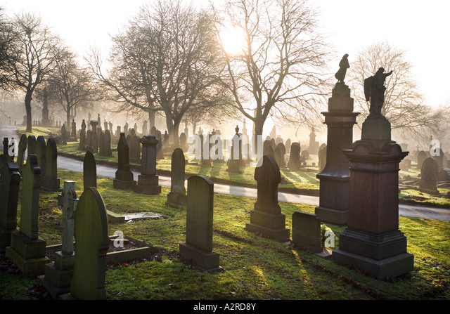 Low winter sunlight flooding through a misty cemetery in Stoke on Trent Staffordshire UK - Stock Image