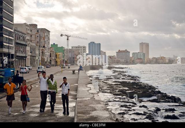 Young boys and girls walking by the wall of El Malecon Havana Cuba - Stock Image