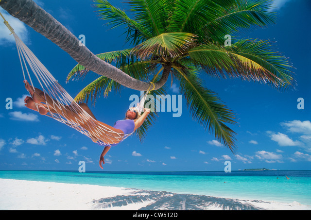 Woman in hammock under palm tree in idyllic holiday setting - Stock Image