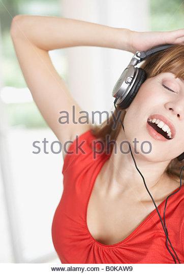 Woman wearing headphones and dancing - Stock Image