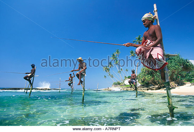 Fishermen fishing on beach against sky Sri Lanka - Stock Image