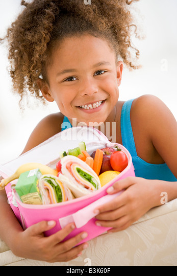 Young girl holding packed lunch in living room smiling - Stock Image