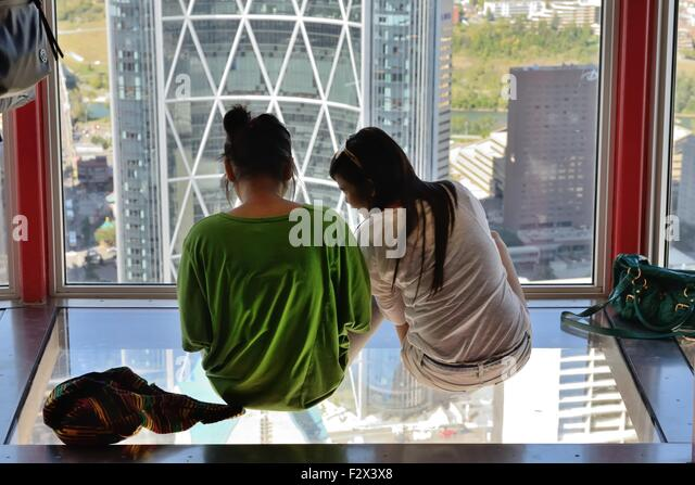 two-teenage-girls-sitting-on-the-glass-f