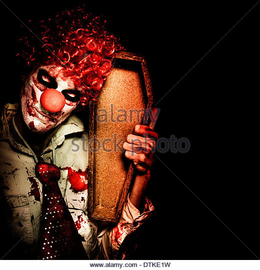 Grim Reaper Death Clown Holding Empty Wooden Casket When Collecting The Dead On Dark Background - Stock Image