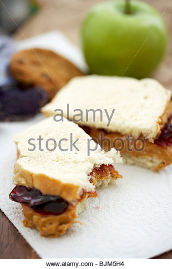 Partially Eaten Peanut Butter and Jelly Sandwich on White Bread, Bagged Lunch - Stock Image