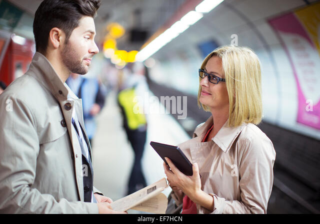 Business people talking in subway station - Stock Image