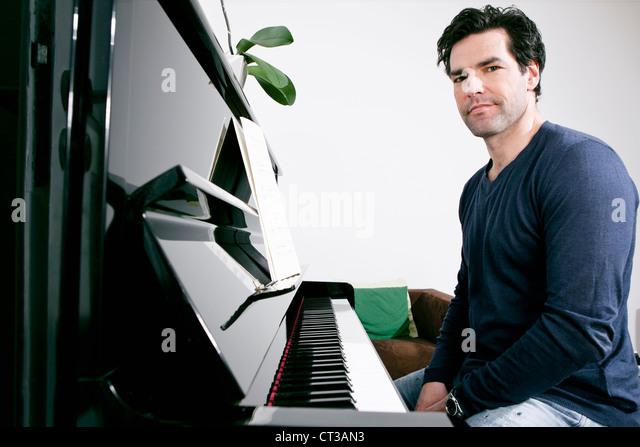 Man sitting at piano - Stock Image