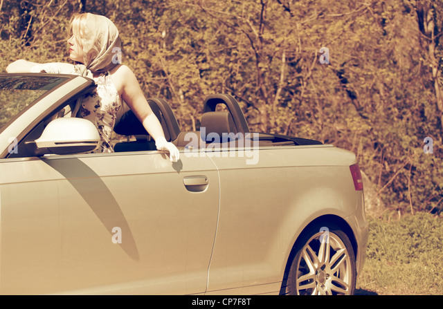 young woman leans out the open roof of a convertible - Stock Image