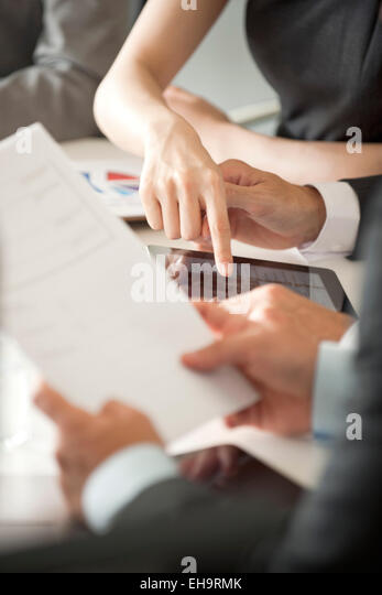 Executives reviewing document in meeting, cropped - Stock Image