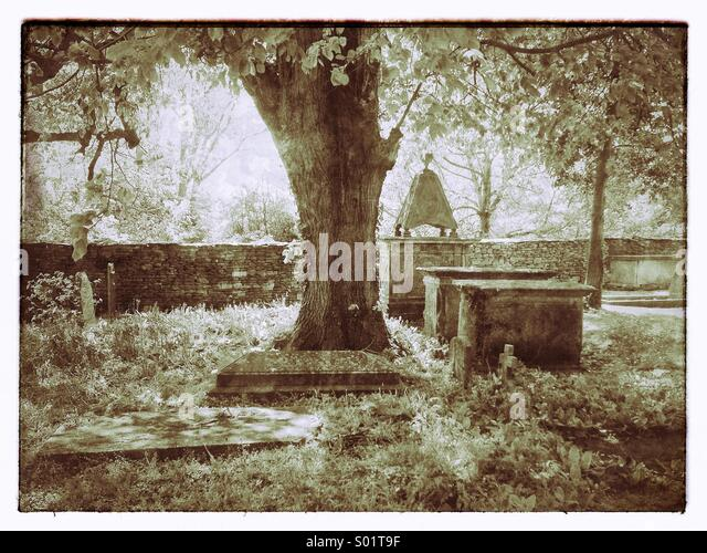 Infrared View of an English Church Graveyard during Springtime. Large tree in centre, tombs & gravestones surround. - Stock Image