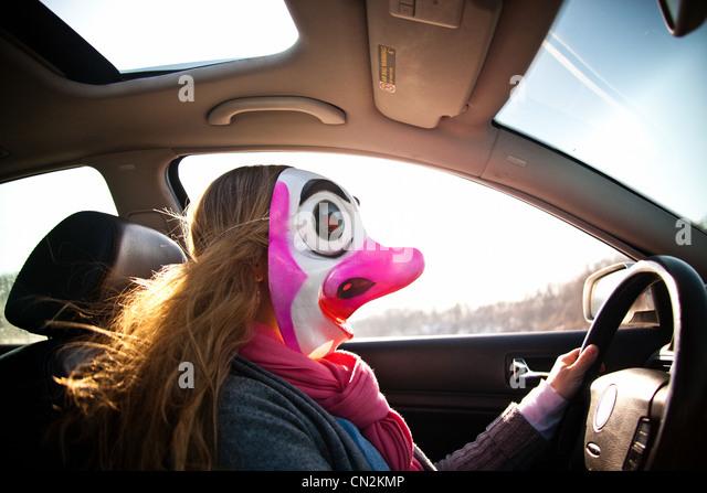 Woman driving car wearing clown mask - Stock Image