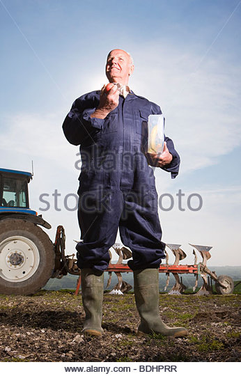 Farmer eating lunch in field with tractor and plough in background - Stock Image