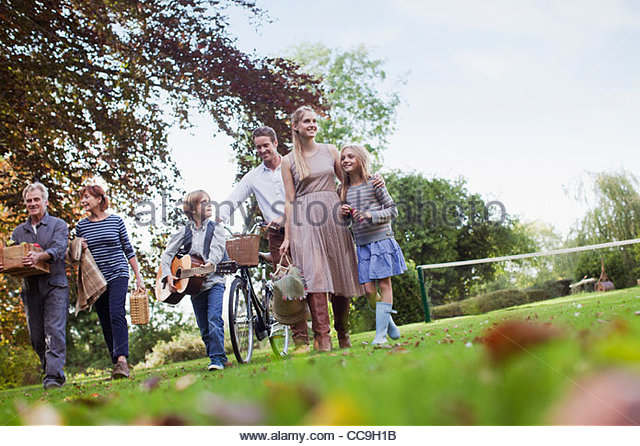 Multi-generation family with picnic baskets walking in park - Stock Image