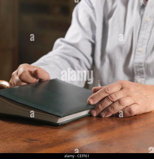 Older man holding book - Stock Image