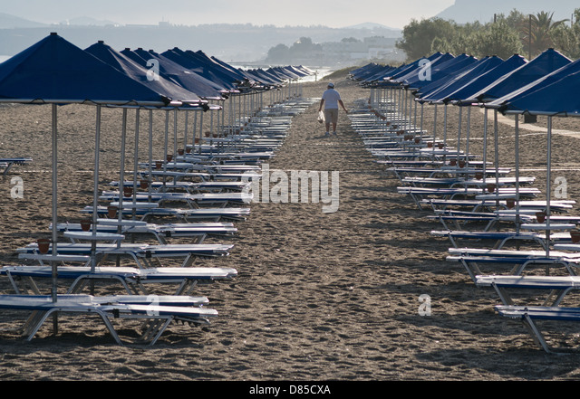 empty-beach-sunbeds-with-solitary-male-f