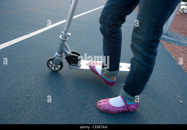 Girl wearing pink sandals riding a scooter - Stock Image