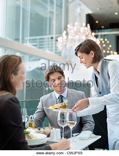 Waitress serving food to couple in restaurant - Stock Image